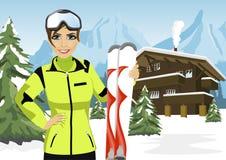 站立在冬天滑雪胜地的瑞士山中的牧人小屋前面的女性山滑雪者 库存例证