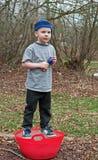 站立在冰冷的红色桶的五岁的男孩 免版税图库摄影