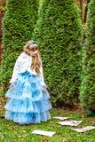 站立在冷杉木附近和看下来纸牌的一个小美丽的女孩 免版税图库摄影