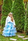站立在冷杉木附近和看下来纸牌的一个小美丽的女孩 免版税库存图片