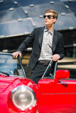 站立在减速火箭的敞蓬车汽车附近的时尚人 图库摄影