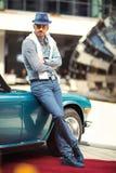 站立在减速火箭的敞蓬车汽车附近的时尚人 免版税库存照片