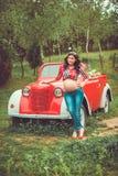 站立在减速火箭的红色汽车前面的妇女 图库摄影