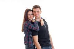 站立在凝视和微笑和拥抱的迷人的夫妇女孩附近人 免版税图库摄影
