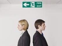 站立在出口标志下的企业同事 免版税图库摄影