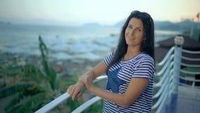 站立在别墅大阳台的愉快的微笑的妇女享受暑假 影视素材