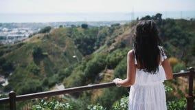 站立在别墅大阳台的白色礼服的少妇看城市 股票录像