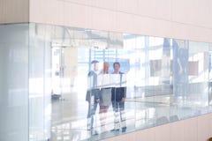 站立在前景的女商人在办公室 免版税库存图片