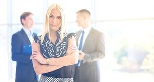 站立在前景的女商人在办公室 库存照片