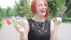 站立在前面的边路的黑礼服的红发女孩 股票视频