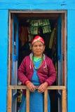 站立在前面蓝色门的传统服装的夏尔巴妇女 库存图片