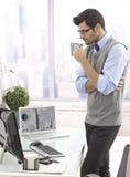 站立在办公室的商人饮用的咖啡 免版税库存照片