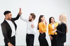 站立在办公室的微笑的同事企业队给一高五 免版税库存图片