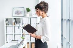 站立在办公室的美丽的女性干事在她的工作场所,拿着计划者,读时间表的天,侧视图 免版税图库摄影