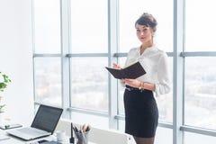 站立在办公室的美丽的女性干事在她的工作场所,拿着计划者,读时间表的天,侧视图 库存图片