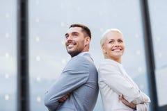 站立在办公楼的微笑的商人 免版税图库摄影