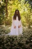 站立在加州的一个森林里的长的白色礼服的美丽的妇女 免版税库存图片
