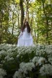 站立在加州的一个森林里的长的白色礼服的美丽的妇女 库存图片