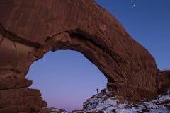 站立在北部窗口曲拱的人在晚上在冬天 免版税库存照片