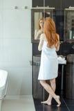 站立在卫生间里的红头发人妇女 免版税库存照片