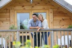 站立在原木小屋大阳台的愉快的夫妇  免版税库存图片