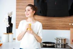 站立在厨房和饮用的橙汁的愉快的妇女 库存图片