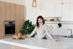 站立在厨房用桌附近的女孩 明亮,白色厨房 愉快的微笑的女孩在厨房里 厨房 库存照片
