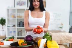 站立在厨房的女孩在她的手上拿着红色蕃茄束 采取菜沙拉的主妇新鲜的成份 免版税图库摄影