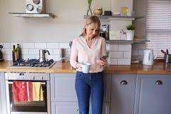 站立在厨房里的妇女发在电话的正文消息 免版税库存照片
