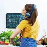 站立在厨房里的妇女,烹调与乐趣a的健康食物 免版税图库摄影