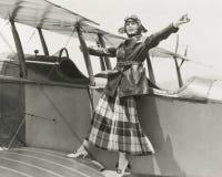站立在双翼飞机的女飞行员 免版税库存照片