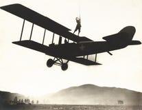 站立在双翼飞机顶部的女替身演员 图库摄影