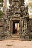 站立在古老墙壁的门道入口的高棉礼服的柬埔寨女孩在吴哥城 免版税库存图片