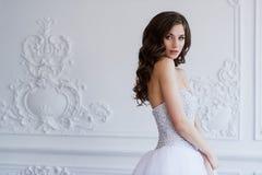 站立在古色古香的内部装饰设计的年轻美丽的新娘完成与造型 古色古香的扶手椅子被雕刻的内部豪华 免版税库存图片