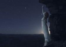 站立在另一个行星峭壁的边缘的妇女  免版税库存照片