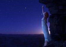 站立在另一个行星峭壁的边缘的妇女  免版税库存图片