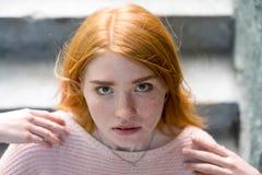 站立在台阶和看照相机的红发女孩 免版税图库摄影