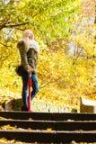 站立在台阶的妇女在秋天公园 免版税库存照片