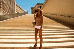 站立在台阶的年轻美丽的女孩,微笑在瓦莱塔在有照片照相机的马耳他,旅行和拍照片的市 免版税库存图片