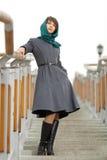 站立在台阶的灰色外套的美丽的时髦的妇女 图库摄影