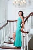 站立在台阶的长的蓝色礼服的妇女 免版税库存图片