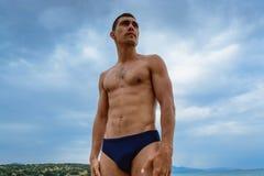 站立在司比杜的海滩的肌肉人 自由,力量,体育,健康生活方式的概念 免版税库存照片