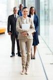 站立在同事前面的年轻女实业家 免版税库存照片