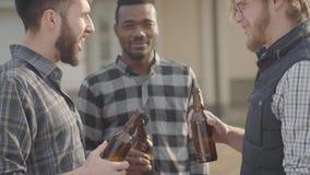 站立在后院饮用的啤酒的三白种人和非裔美国人的人画象  人使他们的瓶叮当响 股票录像