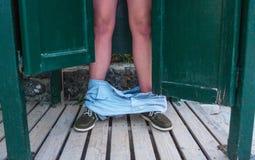 站立在后面的一个人门户开放主义 跌倒从他的腿的人内裤下来对木地板 窃取 图库摄影