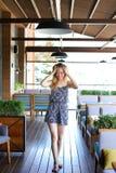 站立在咖啡馆在绿色植物附近和使用与头发的女性 免版税库存照片