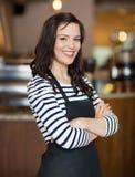 站立在咖啡馆的愉快的女服务员 免版税库存照片