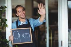 站立在咖啡馆门的侍者拿着有开放标志的黑板 库存照片