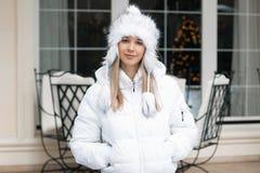 站立在咖啡馆附近的冬天夹克的俏丽的妇女 免版税库存照片