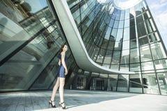 站立在商业中心的大厦的附近美丽的妇女 免版税库存图片